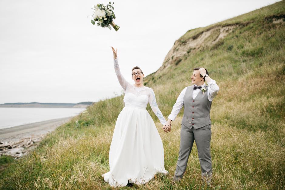 bride throws bouquet on a bluff