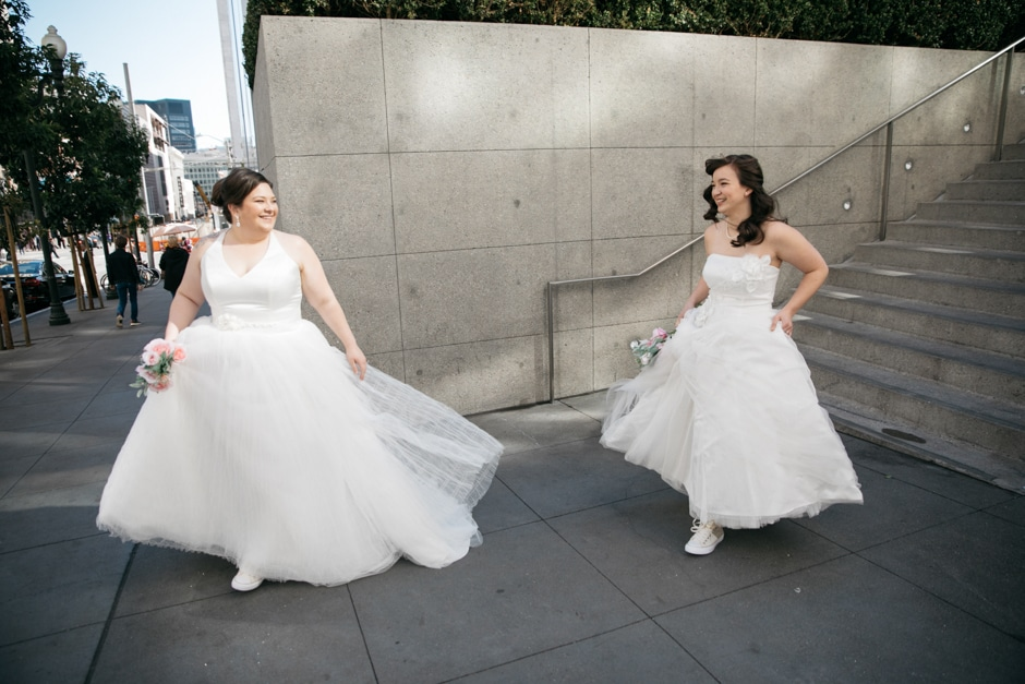 brides running down street in san francisco