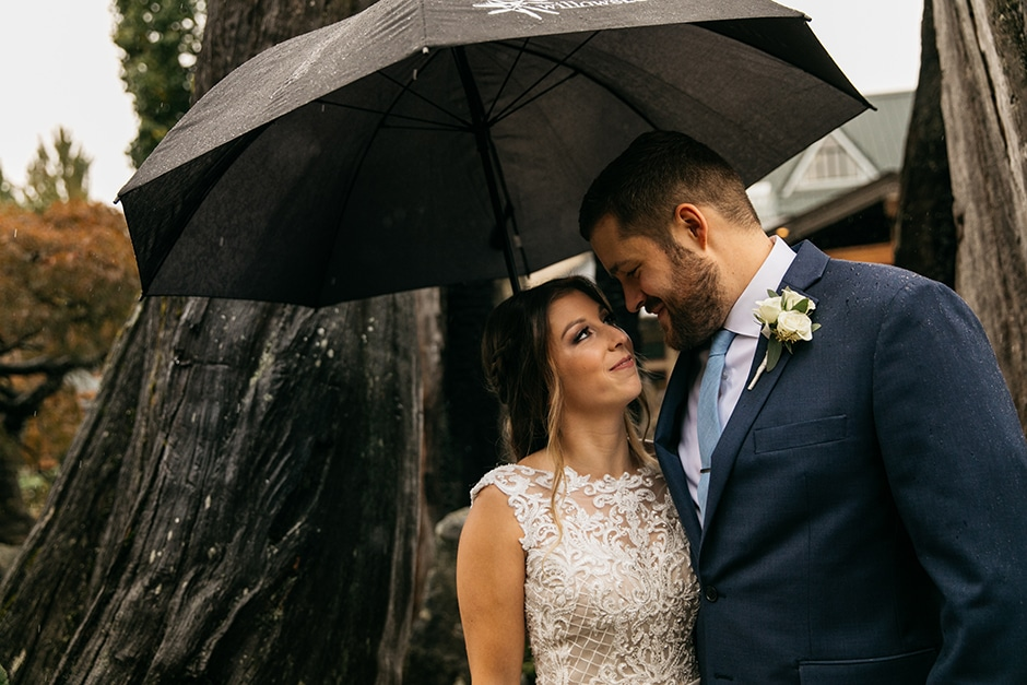 bride groom under umbrella at willows lodge