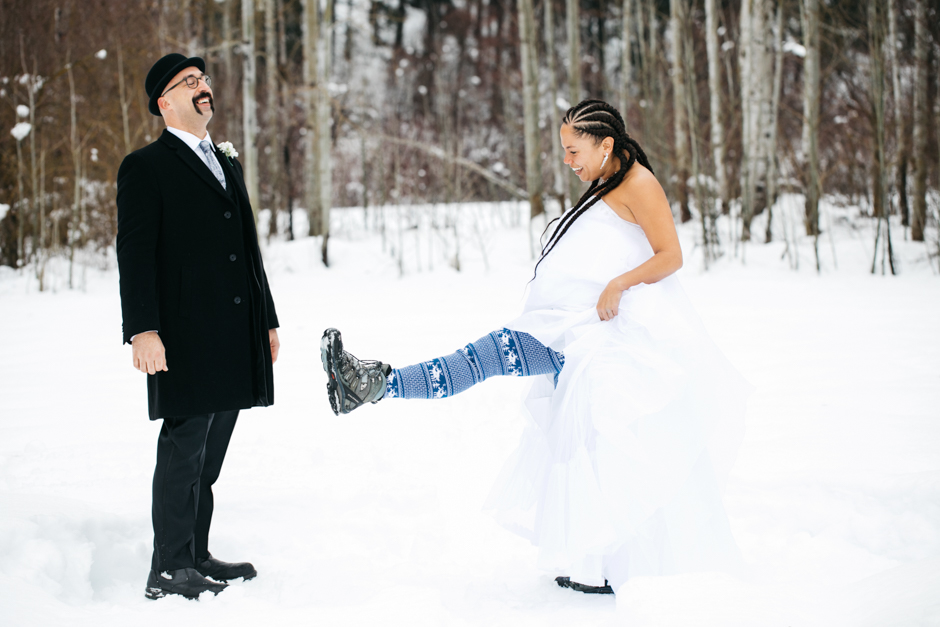 bride showing off boots to groom in the snow