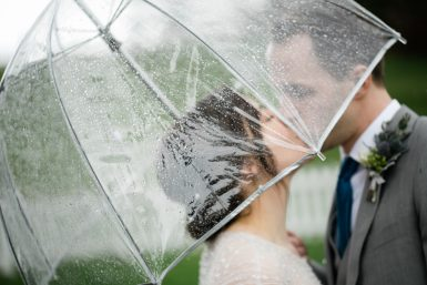 bride groom kissing under an umbrella at their port gamble wedding