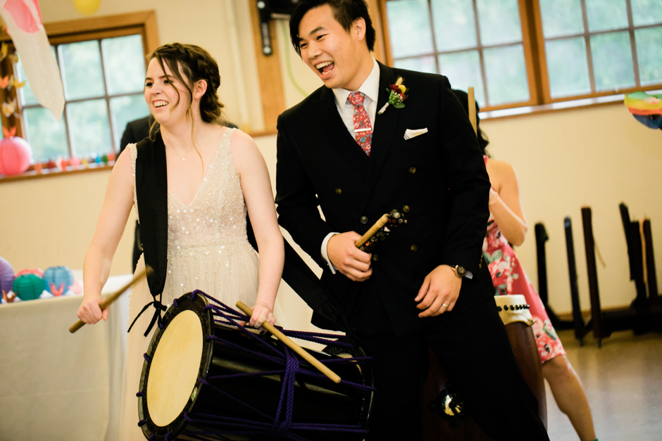 groom and bride taiko drumming during wedding reception