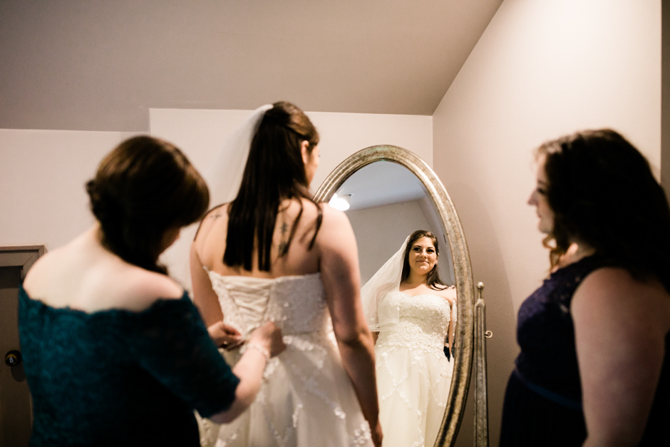 bride with mother and sister getting dressed