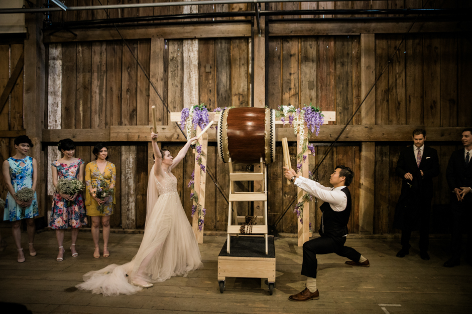 bride and groom playing taiko drums during ceremony