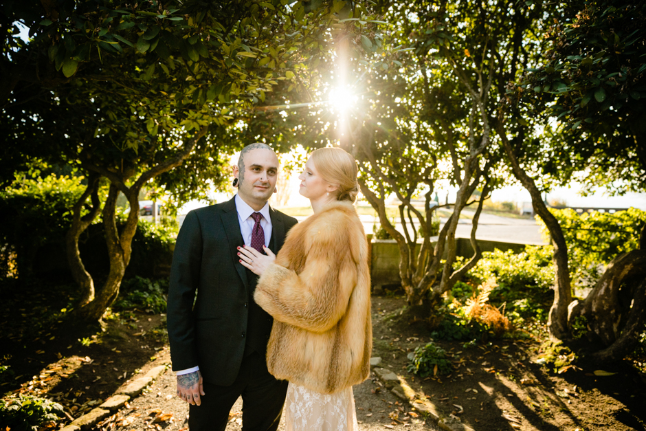 groom and bride standing in parsons garden as the sun peeks through the trees