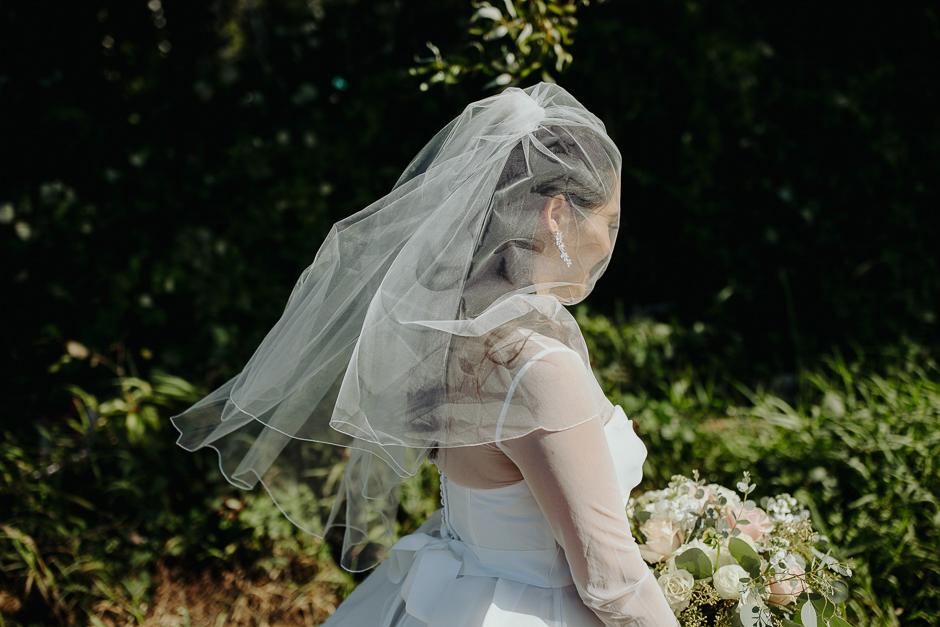 bride in veil walking toward groom on lake washington beach