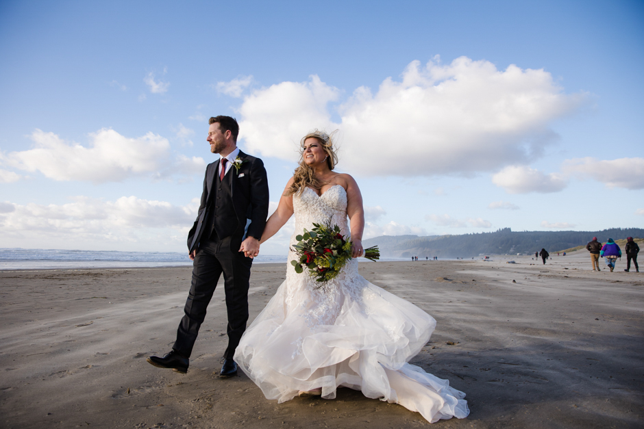 Bride and groom walk along water at Cannon Beach wedding