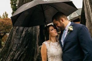 bride groom under umbrella at willows lodge
