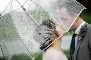 bride groom kissing under an umbrella at their port gamble wedding